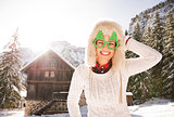 Smiling woman in a funny Christmas glasses near a mountain house