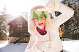 Woman in Christmas glasses framing with hands in the countryside
