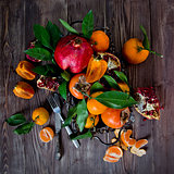 Fresh fruits on a wooden background. Raw and vegetarian eating frame. Sliced orange, persimmon, tangerine, pomegranate.