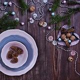 Christmas table place setting with pine branches and plate, ribbon. wooden holidays background
