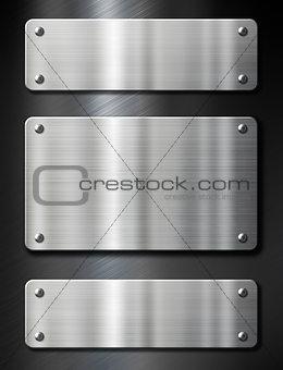 three metal plates on black brushed background