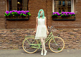 Young girl standing near a bicycle