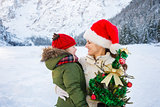 Happy mother and child with Christmas tree in front of mountains