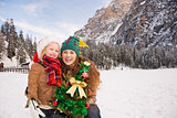 Smiling mother and child with Christmas tree into the mountains