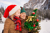 Mother and child looking on Christmas tree in front of mountains