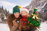 Mother and child with Christmas tree checking photos in camera