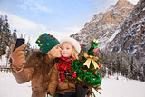 Mother and child with Christmas tree taking selfie outdoors