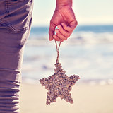young man with a christmas star on the beach, filtered