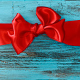 red ribbon bow on a blue wooden surface