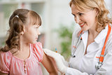 Positive pediatrician doctor vaccinating or inoculating preschool child