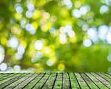 Wooden floor and green forest bokeh blur background