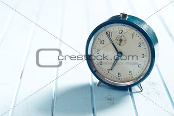 analog alarm clock on wooden table