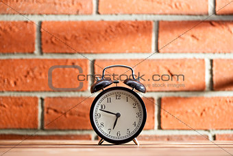 old clock in front of a brick wall
