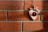 wooden heart hanging on brick wall