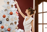 elegant woman decorating xmas tree