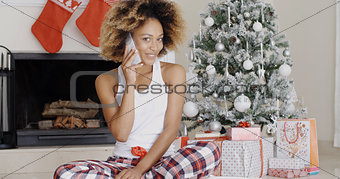Attractive woman phoning her friends at Christmas