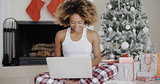 Woman using a laptop in front of the Xmas tree