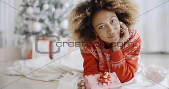 Thoughtful young woman with a Christmas gift