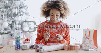Attractive young woman wrapping Christmas gifts