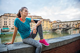 Fitness young woman sitting next to river with earphones