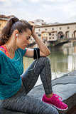 Woman in sportswear sitting with closed eyes and listening music