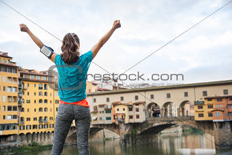Fitness female rejoicing in front of Ponte Vecchio, Italy
