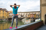 Relaxed fitness woman standing in front of Ponte Vecchio