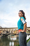 Relaxed athletic woman standing in front of Ponte Vecchio