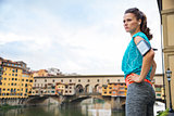 Fitness woman in sportswear staying next to Ponte Vecchio bridge