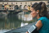 Young fitness female with mp3 player staying close to Arno river