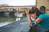 Thoughtful athletic female staying next to Ponte Vecchio bridge