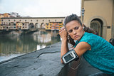 Sportswoman with headset staying in front of Ponte Vecchio