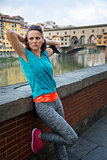 Ð¡oncentrated sportswoman is relaxing in front of Ponte Vecchio