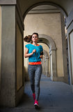 Fitness female with earphones is jogging outdoors