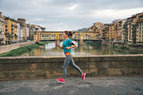 Young female jogger with headset is running by Arno riverside