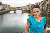 Fitness woman with headset staying in front of Ponte Vecchio
