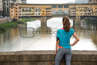 Fitness female in sportswear looking on Ponte Vecchio