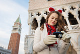 Woman tourist checking photos while on Christmas Venice
