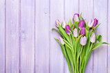 Purple tulips over wooden table