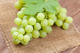 Bunch of white grapes with leaves over burlap