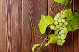 Bunch of white grapes with leaves on wood
