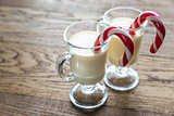 Two glasses of eggnog with candy canes