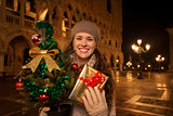 Woman with Christmas tree and gift box on Piazza San Marco