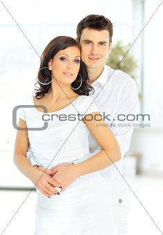 man hugs a woman looking at the camera