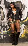 Black Urban girl in sexy hooded outfit by graffiti wall