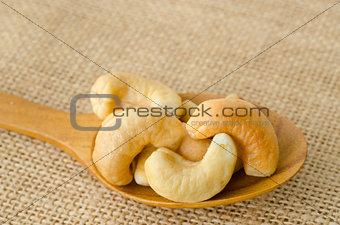 Cashew in wooden spoon.