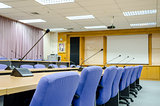The microphones in front of empty chairs in meeting room.