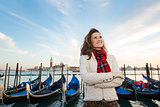 Happy woman traveler standing on embankment in Venice, Italy