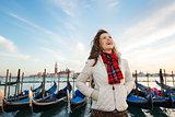 Happy woman traveler standing on embankment in Venice, Italy