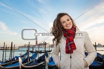 Portrait of happy woman traveler on embankment in Venice, Italy